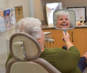 Diana looking at her dentures in the mirror